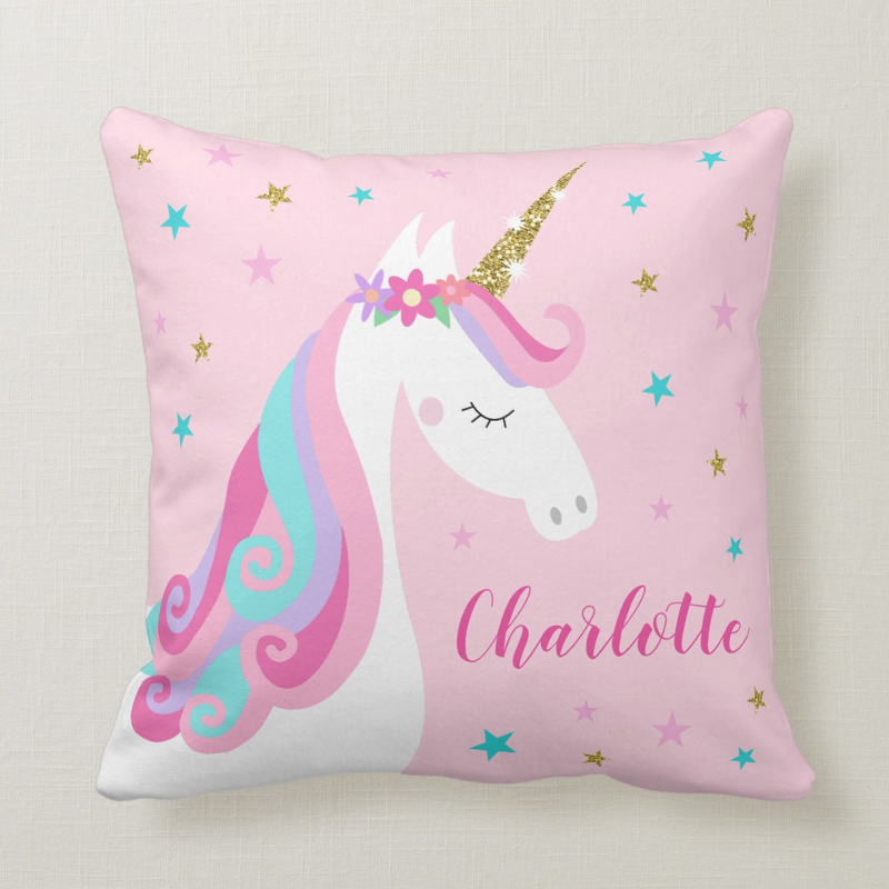 Unicorn pillow with flowers and gold glitter, pink background with stars and personalized name.